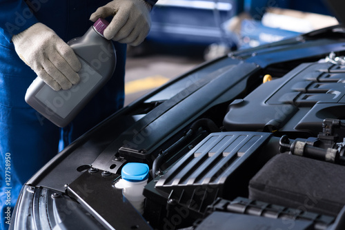 Foto  Professional mechanic changing oil