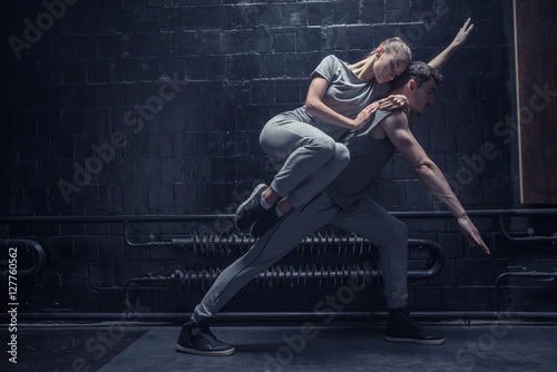 Fototapeta Young dancer lying on the back of other athlete