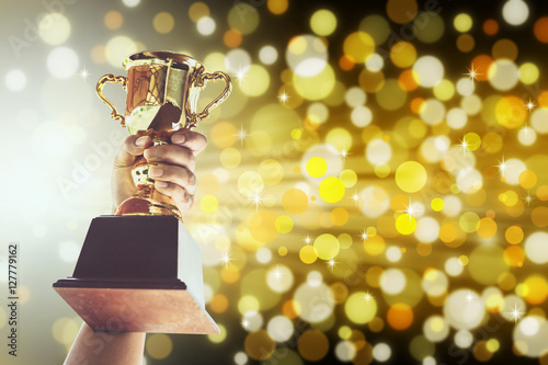 Man holding up a gold trophy cup,win concept. Fototapet