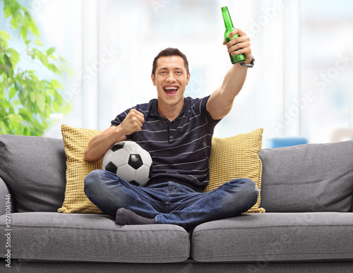Cheerful young man sitting on sofa watching football and having