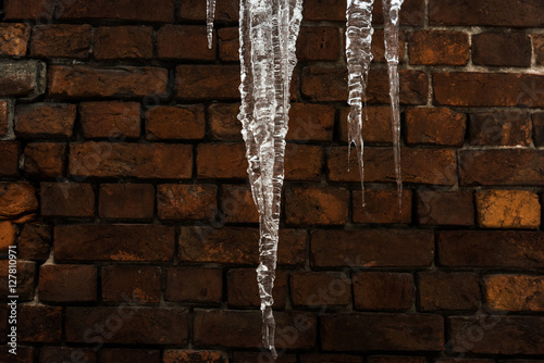 Winter background. Icicles close-up on a brick wall Wallpaper Mural