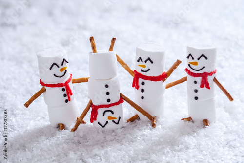 Fotografering  Happy funny marshmallow snowmans on snow