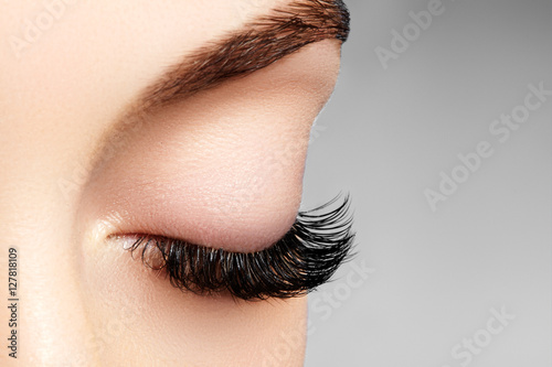 Fotografering  Beautiful macro shot of female eye with extreme long eyelashes and black liner makeup
