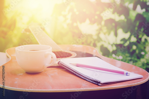 Photo  Acoustic guitars with a notebook and cup of coffee on table,music relax time in