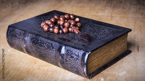 Rosary on the Bible on a wooden background. Holy book.