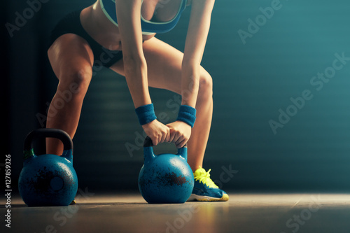 Fotografia  Young fit woman training by kettlebell.