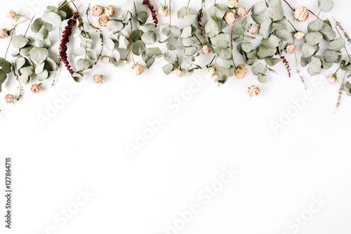 Fototapeta Header. Eucalyptus branches and pink rose buds on white background. Flat lay, top view. Floral composition obraz