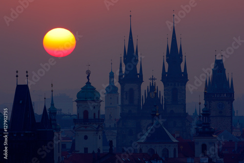Staande foto Praag Beautiful detailed sunrise view of Prague church towers. Early morning colours with old town. Twilight in historical city. Magical picture of tower with orange sun in Prague, Czech Republic, Europe.
