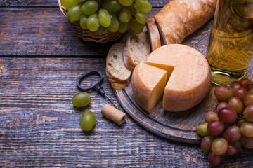White wine in a bottle, cork bottle screw and a set of products - cheese, grapes, nuts, olives, figs on a wooden background