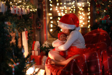 Girl In Santa Hat With  Favorite Toy Doll By  Fireplace, Christm
