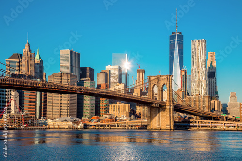 Aluminium Prints Brooklyn Bridge Famous Skyline of downtown New York City at early morning light