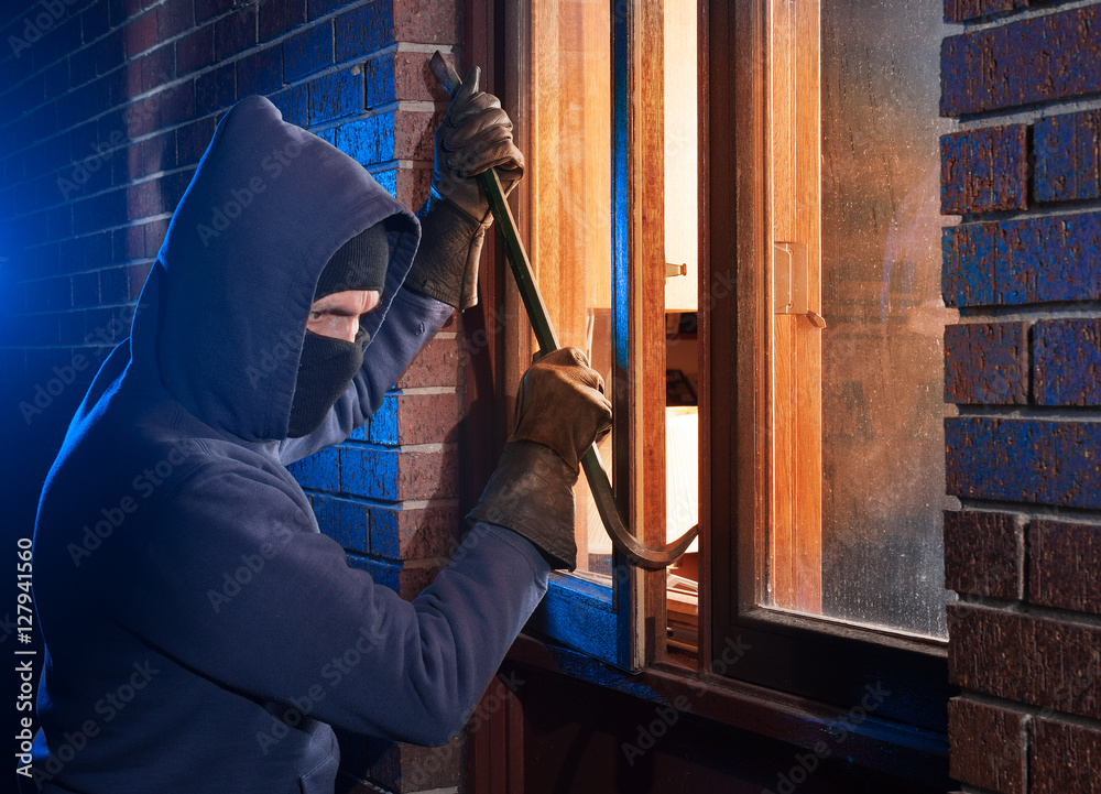 Fototapeta Burglar Using Crowbar To Break Into a House at night with room left and right for type