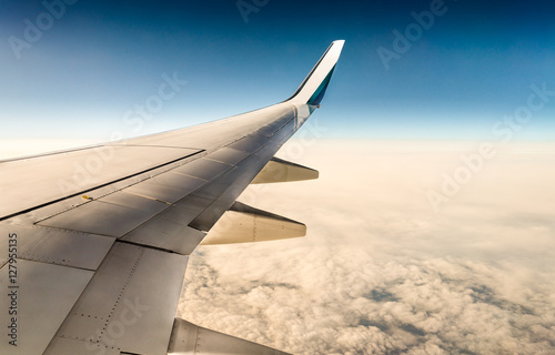 Fotografia  window view of aircraft wing flying over clouds in blue sky (boeing 737)