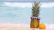Pineapple in sunglasses and orange fruit on sand against turquoise caribbean sea water. Tropical summer vacation concept