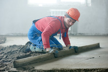 Worker Screeding Indoor Cement...
