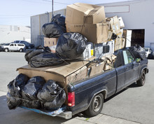 Black Pickup Truck Filled With Recycling Debris.