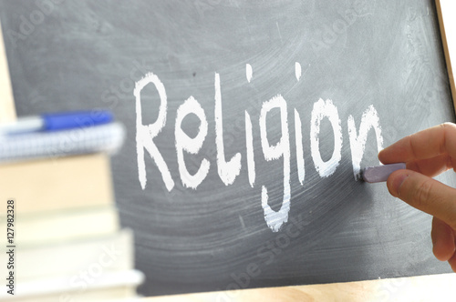 A person writing in a blackboard during Religion class in a school. Next, some books.