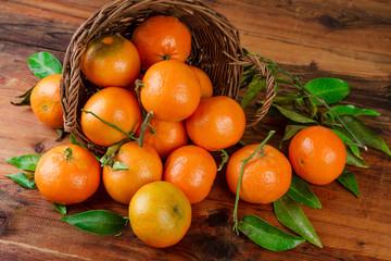 Tangerines basket scattered fruits on woden table