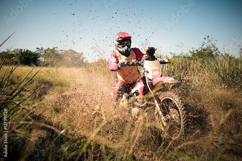Fotomural  Off road dirt bike rider splashing mud in hard enduro rally race