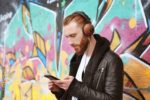 Handsome man in headphones listening to music outdoors