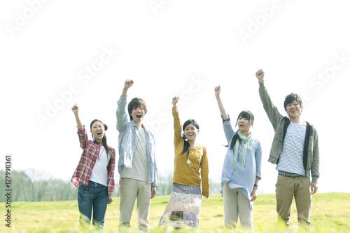 Fotografía  草原で片手を挙げる若者たち