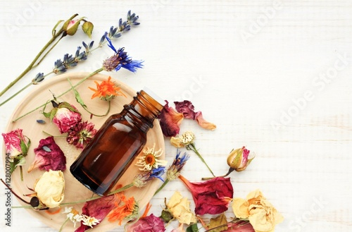 Fotografie, Obraz  Various bright medicinal herb plant on wooden plate, essential oil extract bottle, top view