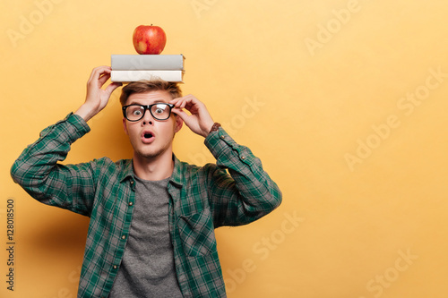 Carta da parati Astonished man student with book and apple on his head