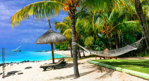 Relaxing tropical holidays with beach chairs and hammock. Mauritius island