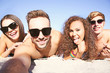 Happy friends taking selfie on beach