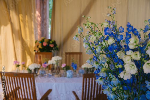 Fototapety, obrazy: Bouquet of white and blue field flowers stands on dinner table