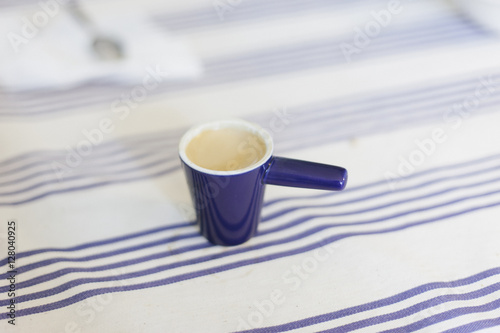 A small blue esspresso cup on a white and blue tablecloth.