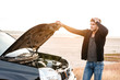 Man holding hands on vehicle hood while standing outdoors