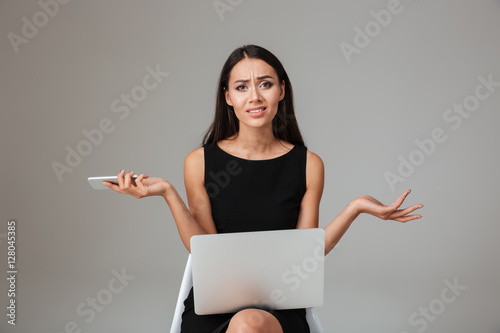 Fényképezés Upset frustrated woman sitting with laptop and holding mobile phone