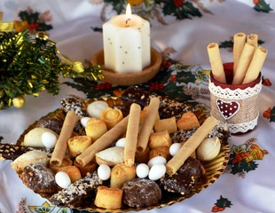 Christmas cookies on a plate and white lighted candle
