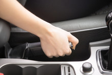 Close Up Of Female Hands Holding A Handbrake Lever To Keep The Vehicle Stationary