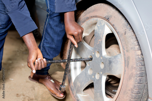 Spoed Foto op Canvas Grill / Barbecue Close-up of mechanic's arms remove the tire of a car.