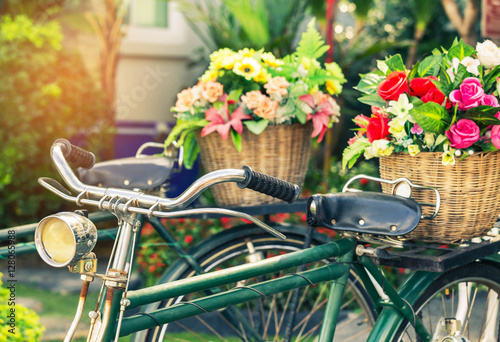 Deurstickers Fiets close up vintage bicycle with bouquet flowers in basket in vintage tone style