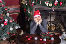 Sad Young Male Seated With Christmas Tree