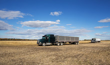 Two Semi Trucks With Attached Grain Trailers Parked In A Harvested Field Under Cloudy Sky In Rural Autumn Landscape