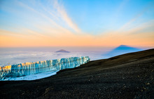 Sunrise Near The Summit Of Mount Kilimanjaro (highest Mountain Of Africa At 5895m Amsl) In Tanzania. Southern Ice Field In The Foreground, Mount Meru And The Shadow Of Kilimanjaro In The Background.