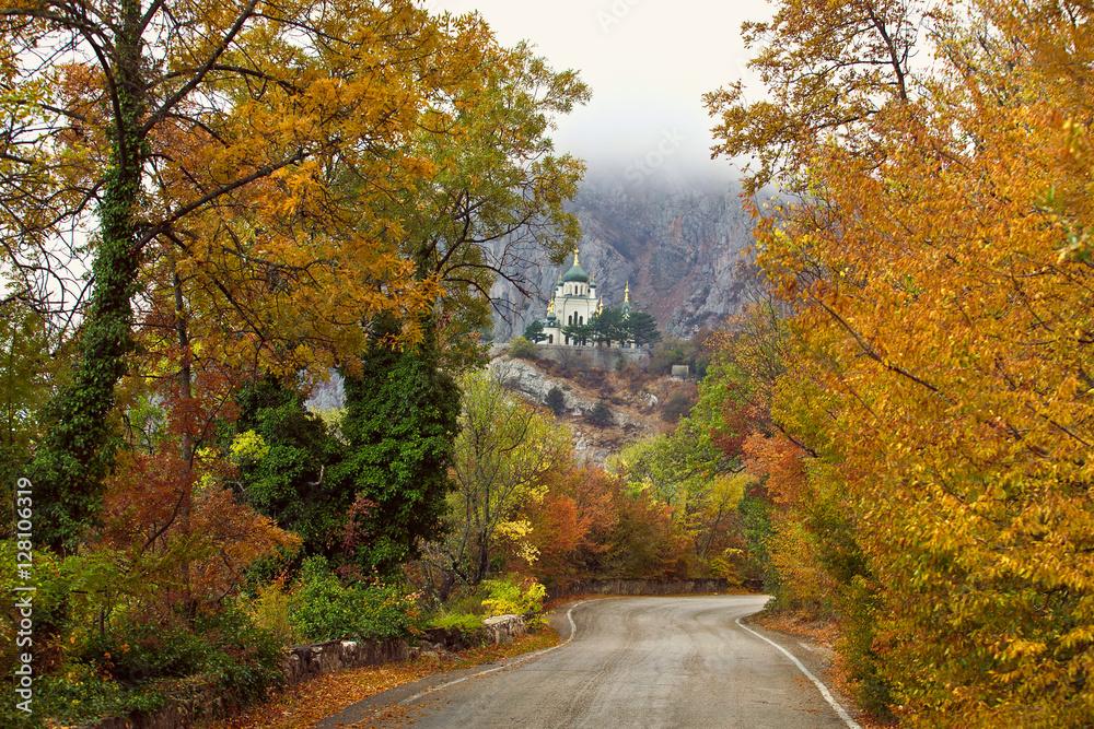 Fototapety, obrazy: Straight mountain road through autumn woods to the church
