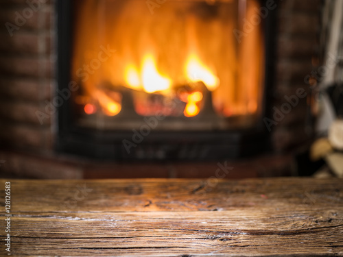 Old wooden table and fireplace with warm fire on the background. Wallpaper Mural