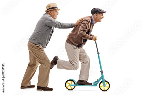 Fotomural  Mature man pushing another man on a scooter