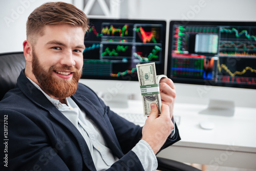 Fotografía Cheerful bearded young businessman sitting and holding dollars