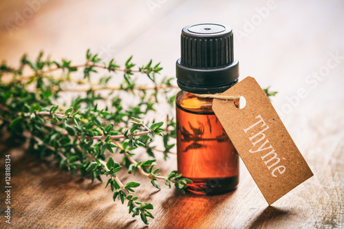 Photo  Thyme oil on wooden background, tag with text