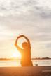 Successful sportsman raising arms on golden sky back lighting su