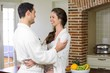 Young couple in bathrobe cuddling each other