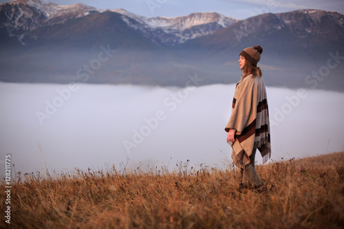 Valokuvatapetti Young woman hiking at mountain peak above clouds and fog Hiker girl wrapping in warm poncho outdoor