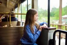 Happy Little Girl Riding A Train In A Theme Park Or Funfair