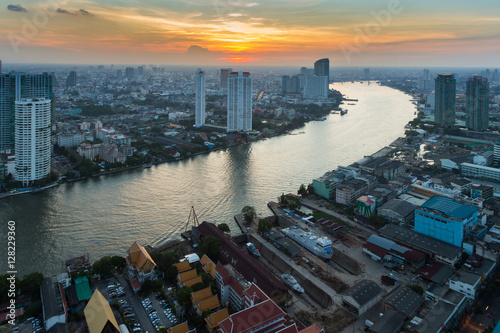 Sunset over river curved skyline, Bangkok business downtown